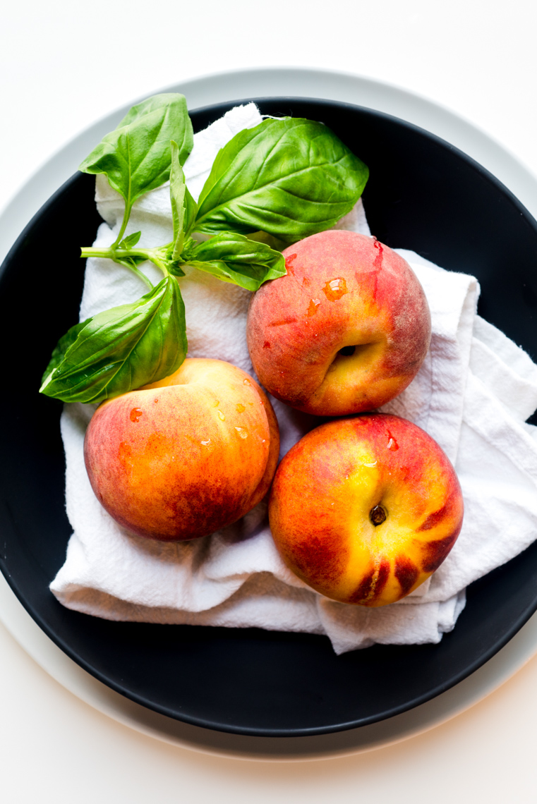 Still Life Photograph of Peaches and Basil in a Black Bowl